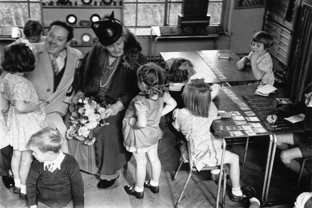 Italian educator Maria Montessori teaching children in a classroom